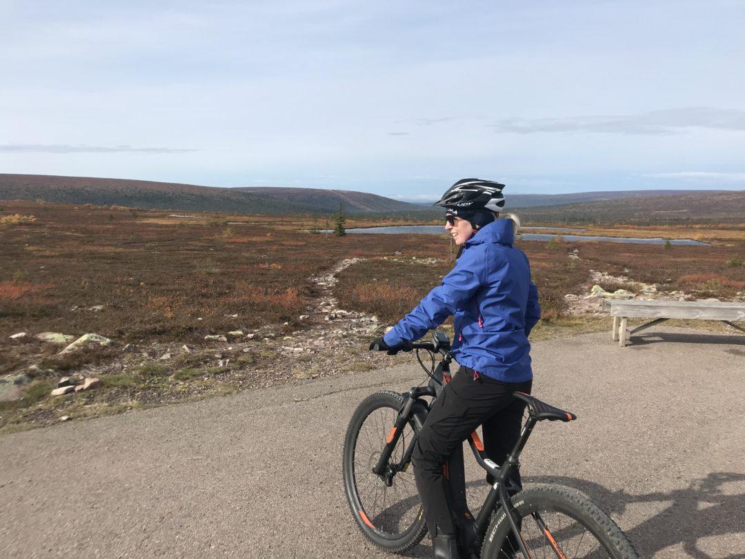 Pernilla Axelsson står med sin elmoutainbike uppe på fjället