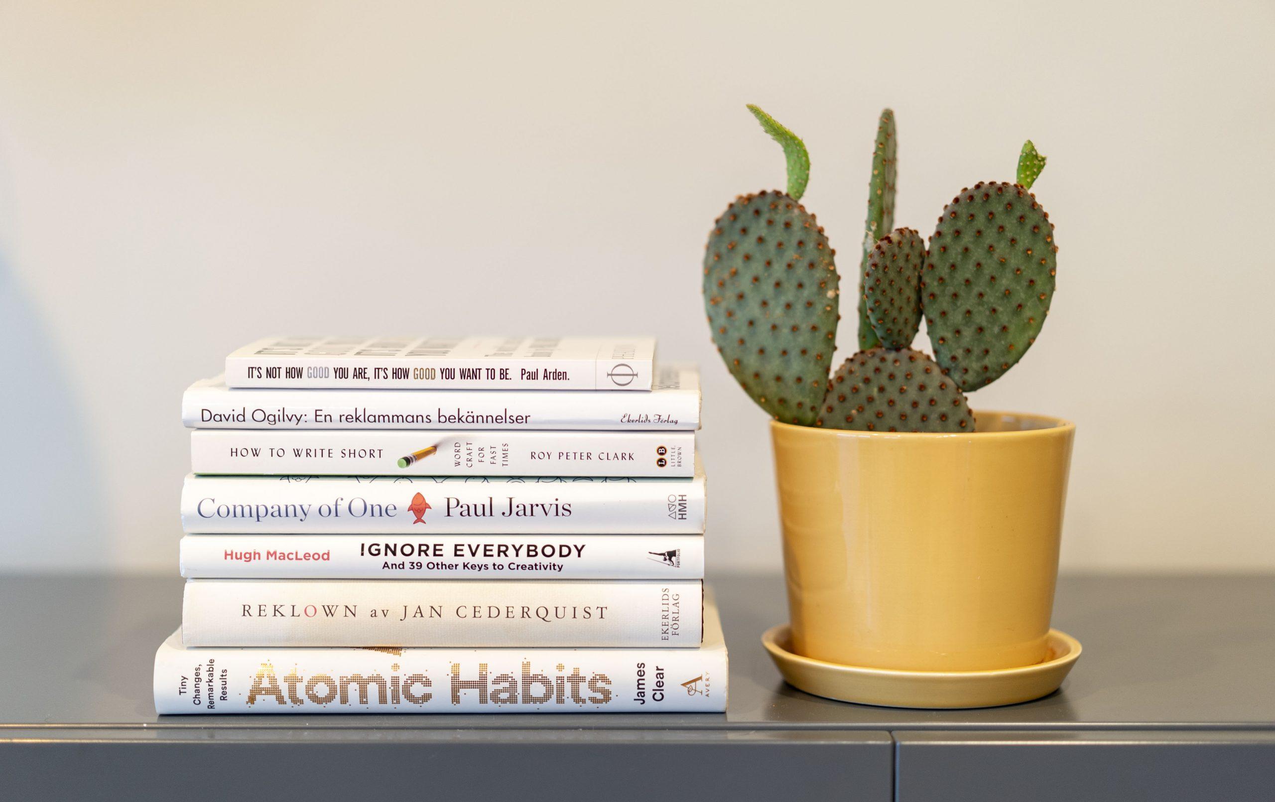 Boken Atomic Habits av James Clear och ett gäng andra böcker ligger på en byrå bredvid en kaktus i en gul kruka