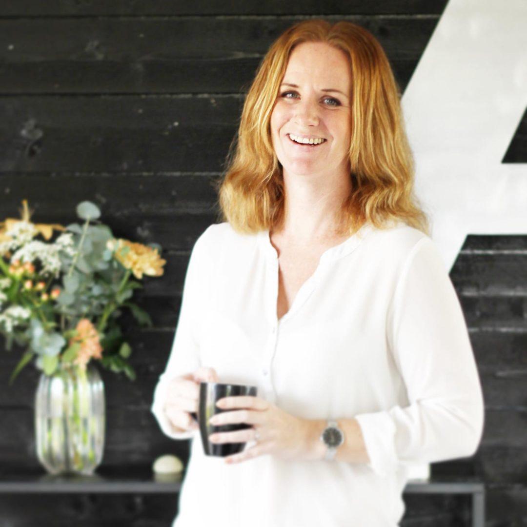 Emma Andreasson ler och håller en kaffemugg i handen