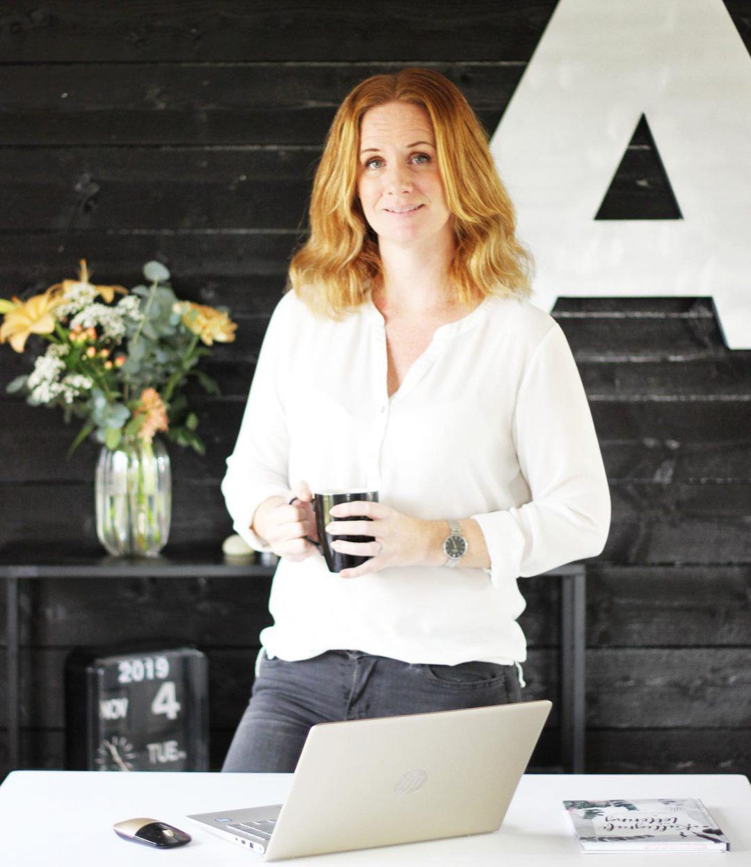 Emma Andreasson står vid datorn med en kopp kaffe i handen
