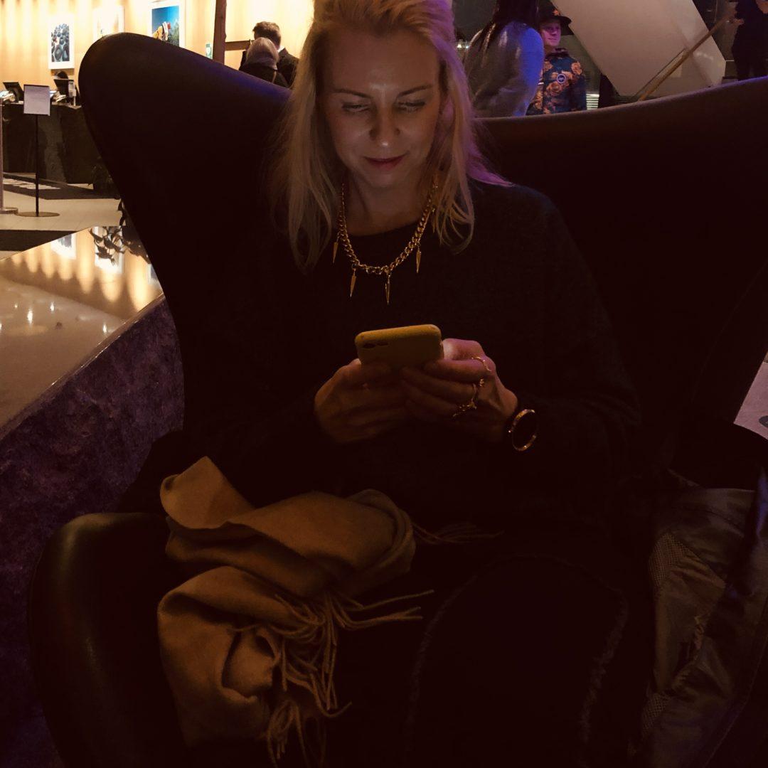 Pernilla Axelsson sitter i en fåtölj och läser en story i mobilen