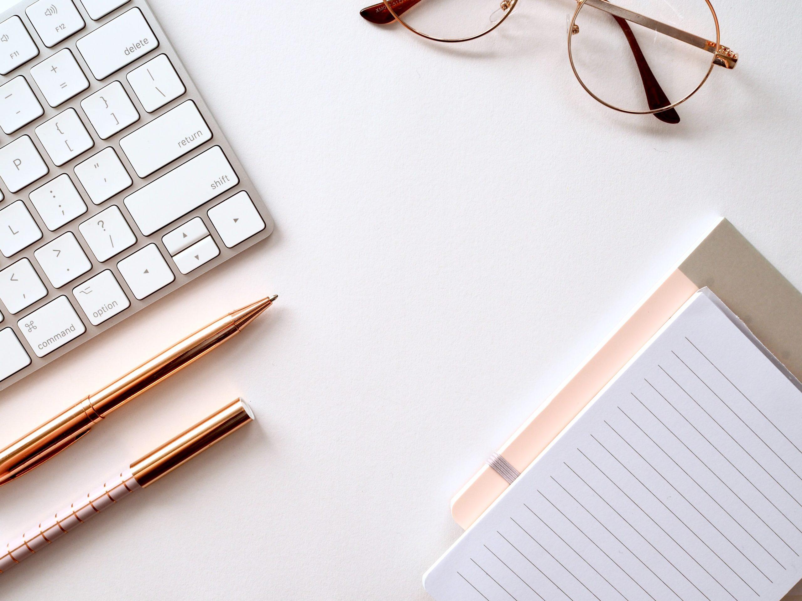 Dekorativ bild med ett tangentbord, ett par glasögon och ett kollegieblock