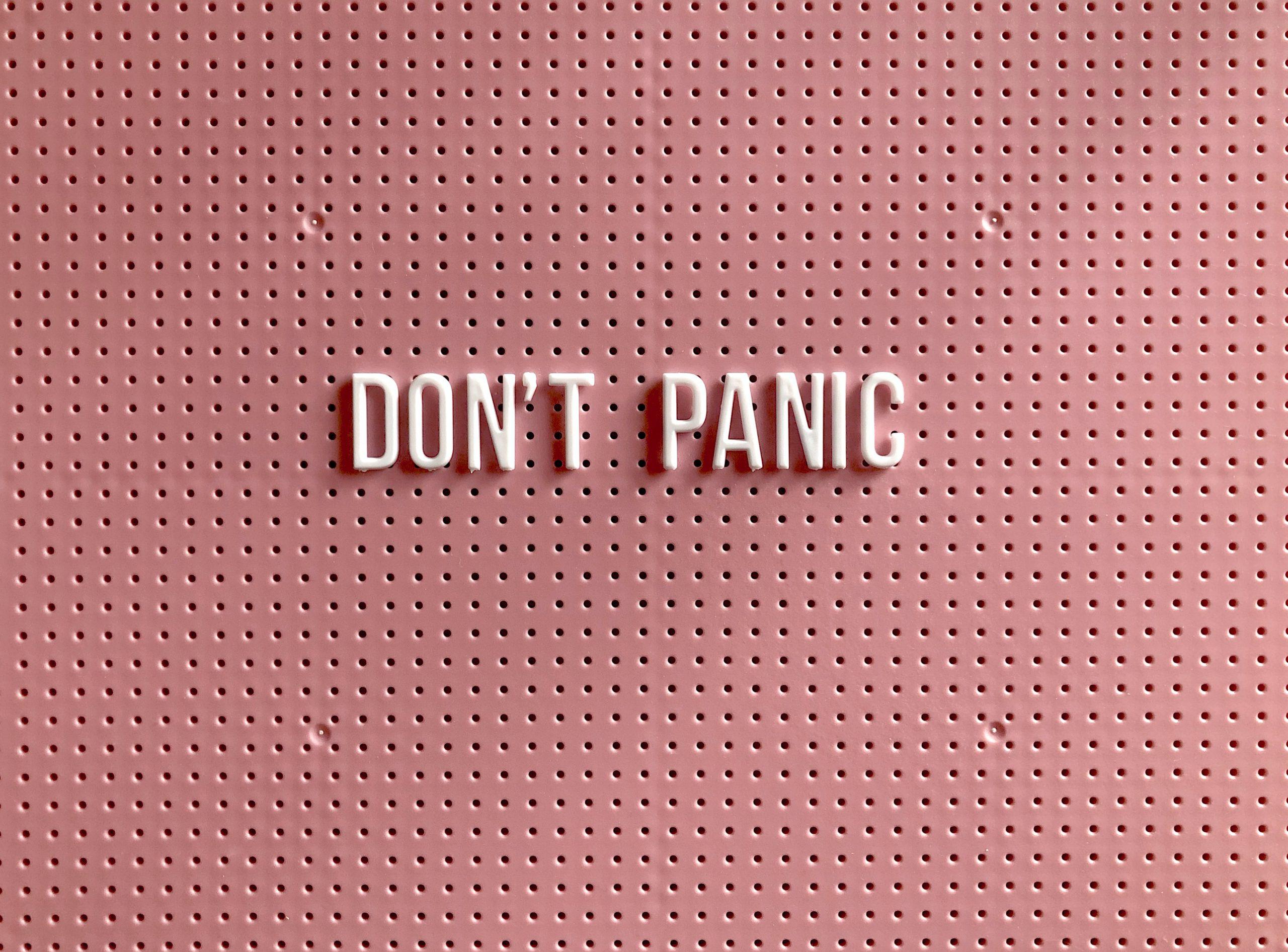 Rosa bakgrund med orden Don't panic i vita bokstäver