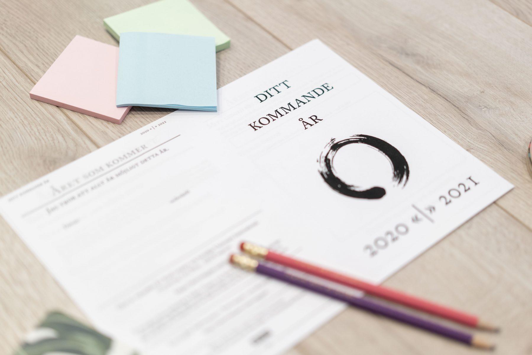 Utskrift av arbetsmaterialet Ditt kommande år, några pennor och post-it-lappar ligger på ett golv
