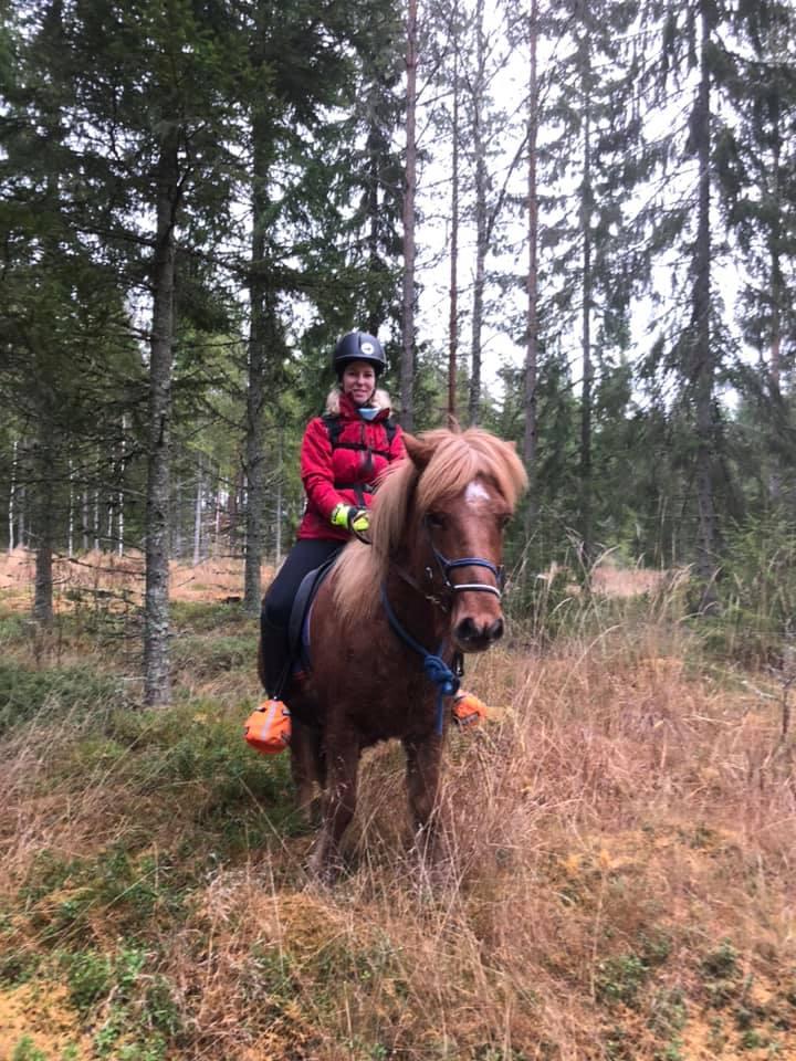 Pernilla Axelsson rider på islandshästen Fossbui i skogen