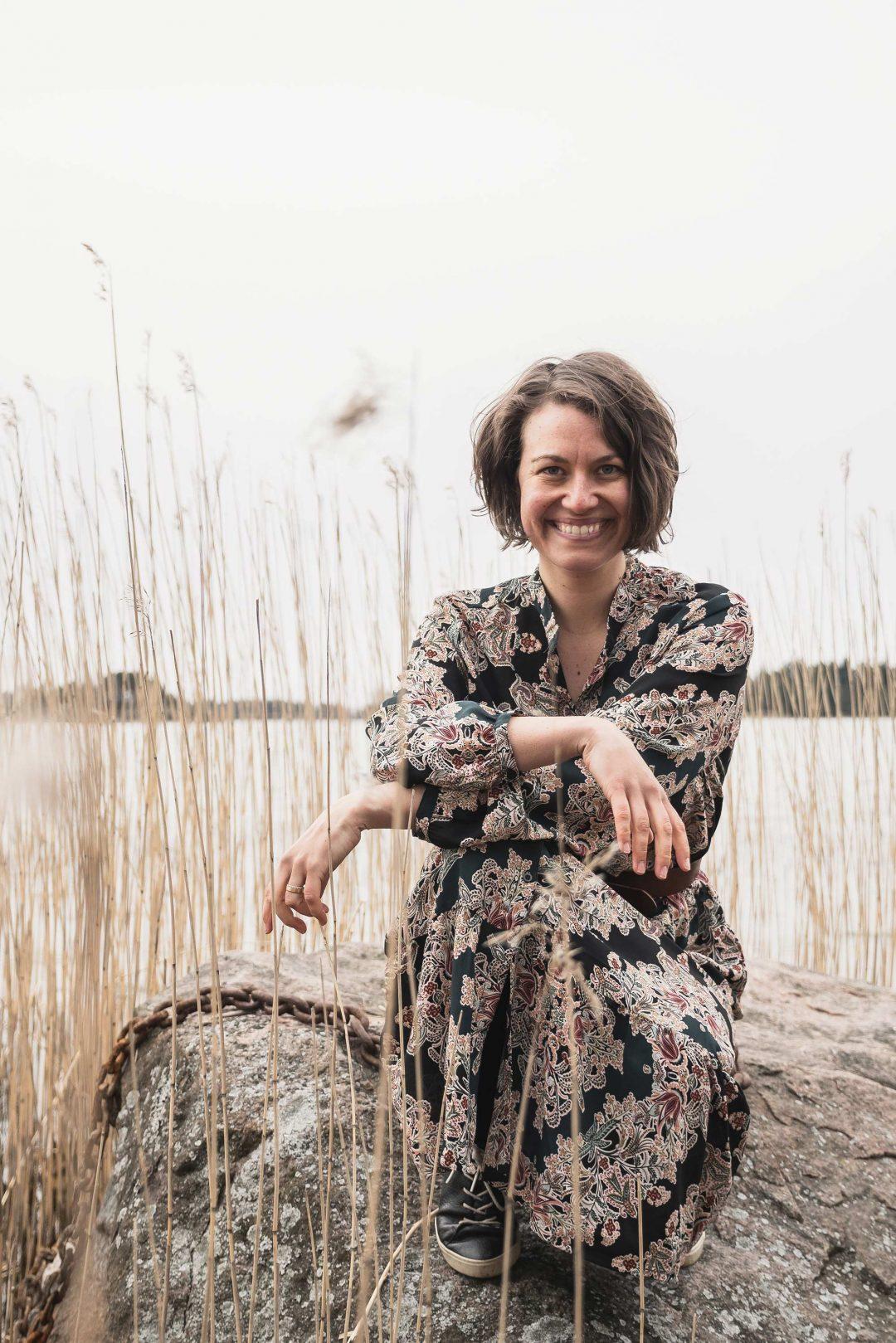 Amanda Backholm sitter på en sten vid havet