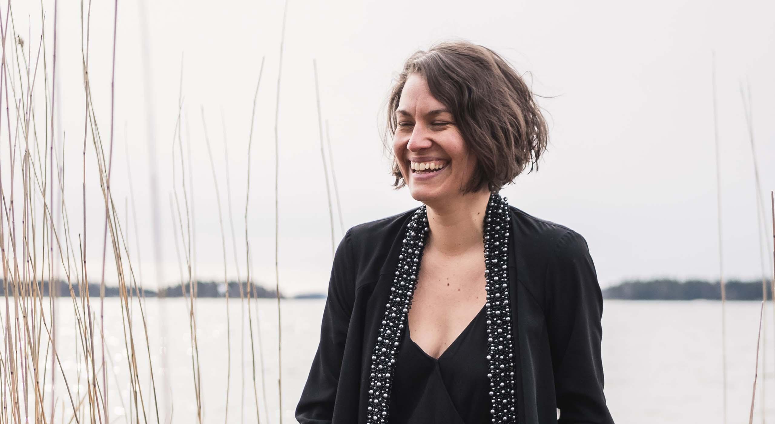 Amanda Backholm sitter och ler vid vattnet